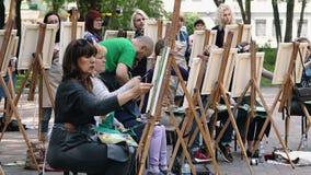 Poltava, Ucrania - puede 2019: Un grupo de mujeres de diversas edades est? aprendiendo dibujar im?genes en el parque almacen de video