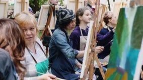 Poltava, Ucrania - puede 2019: Un grupo de mujeres de diversas edades est? aprendiendo dibujar im?genes en el parque metrajes