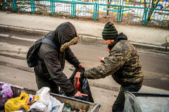 POLTAVA, UKRAINE - 18 FEBRUARY 2016: Two young men near the garbage can collecting paper for recycling. Stock Photos