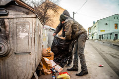 POLTAVA, UKRAINE - 18 FEBRUARY 2016: Two young men near the garbage can collecting paper for recycling. Royalty Free Stock Image