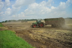 POLTAVA, UKRAINE - 29 JULY 2015: Tractor spreading manure on fields. This procedure allows to collect two harvests a year. Royalty Free Stock Photography