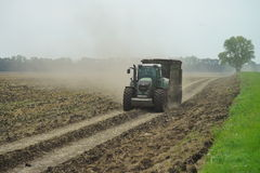 POLTAVA, UKRAINE - 29 JULY 2015: Tractor spreading manure on fields. This procedure allows to collect two harvests a year. Stock Photo