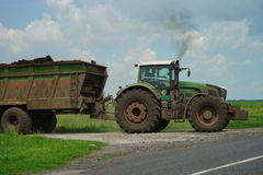 POLTAVA, UKRAINE - 29 JULY 2015: Tractor spreading manure on fields. This procedure allows to collect two harvests a year. Royalty Free Stock Photos