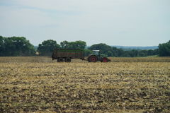 POLTAVA, UKRAINE - 29 JULY 2015: Tractor spreading manure on fields. This procedure allows to collect two harvests a year. Royalty Free Stock Images
