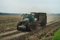 POLTAVA, UKRAINE - 29 JULY 2015: Tractor spreading manure on fields. This procedure allows to collect two harvests a year. Stock Photos