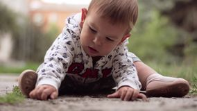 Poltava, Ukraine - 3 September 2019 Baby toddler sitting on the ground and playing . Summer day stock video footage