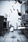 Poltergeist. Utensils, pots and saucepans flying around in a kitchen stock images