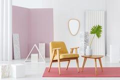 A poltrona amarela e a mesa de centro de madeira com um vaso ajustaram-se no branco fotografia de stock royalty free