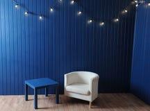 Poltrona bianca del tessuto e tavola blu su un fondo della parete blu con la retro ghirlanda delle lampadine Fotografie Stock Libere da Diritti