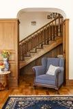 Poltrona blu contro le scale di legno in salone classico inter fotografia stock