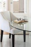 Poltrona con il libro e gli occhiali sulla decorazione interna della tavola Immagine Stock
