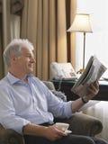 Poltrona de Reading Newspaper In do homem de negócios Foto de Stock