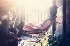 Poltrona di cuoio di seduta della ragazza della foto in Internet moderno della radio del computer portatile di uso e della costru Fotografia Stock Libera da Diritti