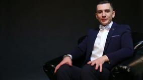 Poltrona di cuoio in una stanza scura ed in un uomo d'affari attraente video d archivio