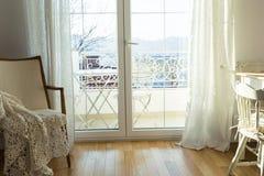 Poltrona do vintage contra a parede branca e a janela grande com cortina fotografia de stock