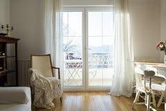 Poltrona do vintage contra a parede branca e a janela grande com cortina imagens de stock