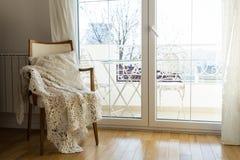 Poltrona do vintage contra a parede branca e a janela grande com cortina imagem de stock