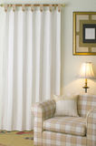 Poltrona e cortina na sala de visitas ocasional Fotografia de Stock