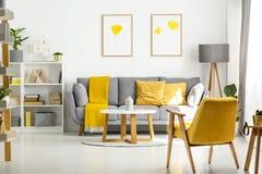 Poltrona e tavola di legno gialle nell'interno del salone con il po fotografia stock libera da diritti