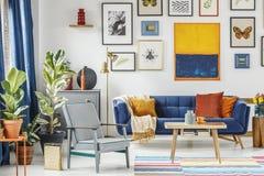 Poltrona grigia accanto alla tavola di legno ed allo strato blu nella Florida artistica Fotografia Stock