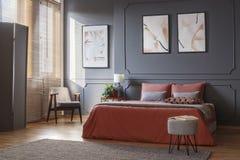 Poltrona grigia e retro che sta nell'angolo di un bedroo elegante immagini stock libere da diritti