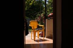 Poltrona plástica nas horas de verão da casa da vila imagem de stock