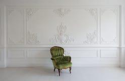 Poltrona verde di lusso d'annata nella stanza bianca sopra gli elementi di roccoco dei modanature dello stucco di bassorilievo di Fotografia Stock Libera da Diritti