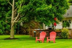 Poltronas vermelhas do país dois de Amish, lanternas antigas que penduram em uma árvore em Lancaster, PA foto de stock royalty free