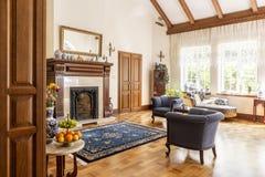 Poltrone blu e tappeto modellato davanti al camino di legno nell'interno specializzato Foto reale immagine stock