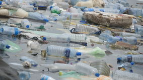 Poluição ambiental Garrafas plásticas, sacos, lixo no rio, lago Desperdícios e poluição que flutuam na água lento video estoque