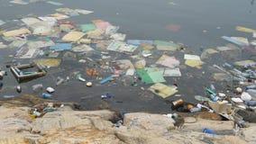 Poluição ambiental Garrafas plásticas, sacos, lixo no rio ou lago Desperdícios e poluição que flutuam na água movimento video estoque