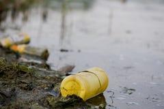 Poluição de água - frasco plástico na superfície do rio imagem de stock royalty free