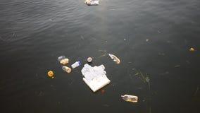 Poluição do ambiente: Lixo de roda que flutua em um rio filme