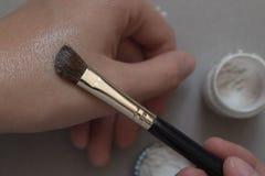 Polvere della perla Mano femminile applicata dall'ombretto della spazzola a disposizione Immagine Stock Libera da Diritti