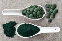 Polvere e compresse di alghe di Spirulina immagine stock