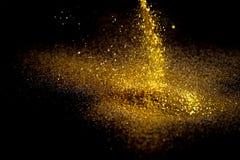 Polvilhe a poeira de ouro em um fundo preto fotos de stock royalty free