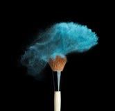 Polvo azul aislado del maquillaje con el cepillo en negro Imagen de archivo