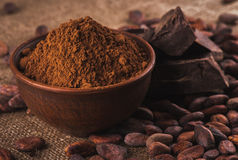 Polvo de cacao en un cuenco de cerámica marrón, granos de cacao crudos en el pis imagen de archivo libre de regalías