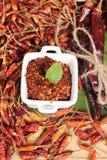 Polvo de chile y pimientas secadas en el fondo de madera Foto de archivo