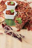 Polvo de chile y pimientas secadas en el fondo de madera Fotografía de archivo