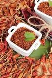Polvo de chile y pimientas secadas en el fondo de madera Fotografía de archivo libre de regalías