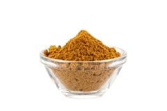 Polvo de curry caliente de Madras en el tazón de fuente de cristal imagenes de archivo