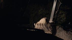 Polvo de Digging Sand And del excavador que trabaja durante obras viales en la noche, cierre encima del tiro del cubo de una exca almacen de metraje de vídeo