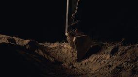 Polvo de Digging Sand And del excavador que trabaja durante obras viales en la noche, cierre encima del tiro del cubo de una exca almacen de video
