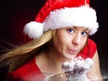 Polvo de la luz de las estrellas de la mujer de la Navidad que sopla Imágenes de archivo libres de regalías