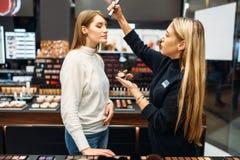 Polvo de prueba del vendedor y de la mujer en tienda del maquillaje imagenes de archivo