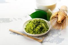 Polvo del té del matcha y accesorios verdes del té en el fondo blanco Imagenes de archivo