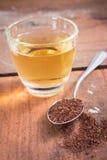Polvo del té y agua de la bebida en vidrio Fotos de archivo libres de regalías