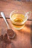 Polvo del té y agua de la bebida en vidrio Fotografía de archivo libre de regalías