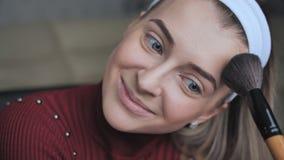 Polvo facial de aplicación rubio a sí misma con un cepillo almacen de metraje de vídeo